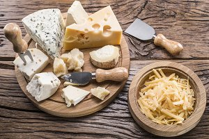 cheeses on a wooden board.