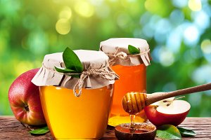 Glass cans full of honey and apples