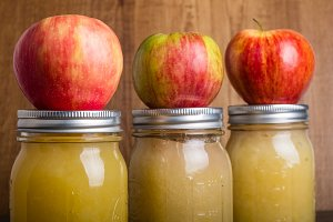 Jars of applesauce with apples