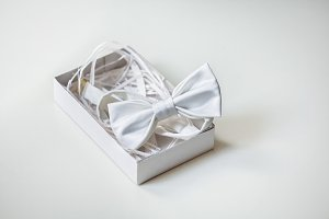 Luxury silk bow-tie in decorated box on light background