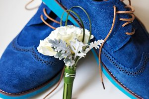 Pair of elegant grooms blue shoes with boutonniere
