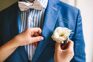 Yellow boutonniere pinned to a grooms jacket