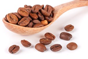 Coffee beans in a wooden spoon isolated on a white background