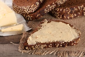slices of black bread with sesame seeds and butter on an old wooden background