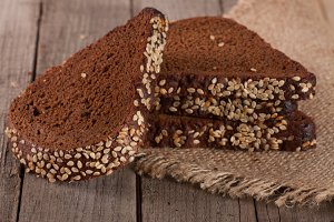 slices of black bread with sesame seedson on the old wooden background