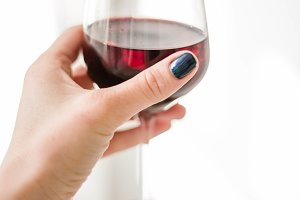 a glass of red wine in hand