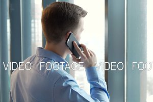 Young businessman talking on cellphone standing by window at coworking office