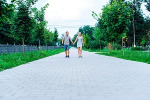 Young modern couple is walking in the park holding hands, in summer in the city, horizontal in full growth, family on nature is resting, the concept of a happy family.