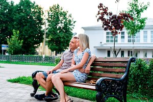 Young modern couple sitting on bench in park hugging, in summer in city, horizontal, family on nature is resting, concept of happy family, lifestyle.