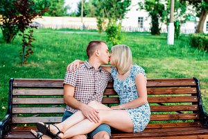 Young modern couple hugging in the park, in summer in the city, horizontal, family in nature resting, concept of happy family, lifestyle. They go to look into the eyes. A declaration of love. Kiss on the bench.