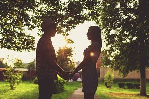 A guy holds his girlfriend by hand, in the summer in the city silhouette against the sunset, the concept of relationship, the newlyweds. Lifestyle, the summer is a guy with a girl. A lot of foliage in the background.
