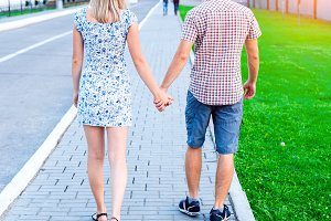Young modern couple in the city, in the summer in full growth, the attitude of adolescents in love, the concept of a happy family, a lifestyle. A declaration of love. They go holding each other's hands.