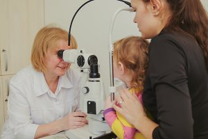Woman optometrist checks eyesight at little girl - child's ophthalmology