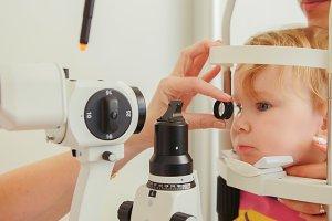 Doctor optometrist checks eyesight at little girl - child's ophthalmology