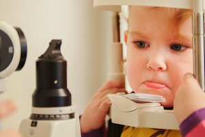 Child's optometry concept - little girl angry when checks eyesight in eye ophthalmological clinic