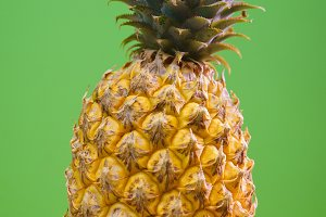 Thai pineapple close-up on a green background