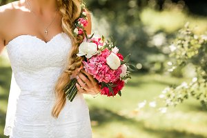 Bride holding delicate marriage bouquet. Beautiful sunny day in park.