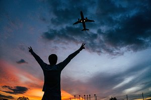 Airplane flying over man, sunset