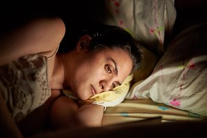 Woman using tablet in bed