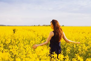 Girl enjoying rapeseed blooming