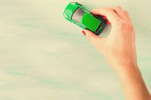 Toy car woman's hand. Purchase insurance loan travel concept