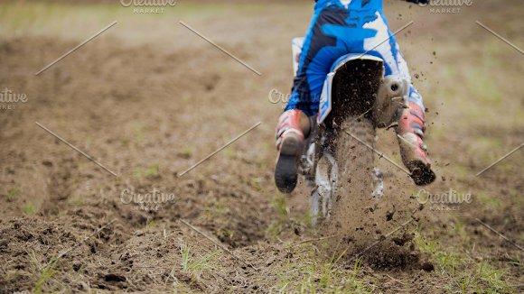 Motocross racer start riding his dirt Cross MX bike kicking up dust rear view, close up