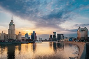 Wide panoramic view photography of evening city landscape with sun over the moscow river at sunset with Stalin Skyscraper and its reflection, outdoor travel background, Moscow, Russia