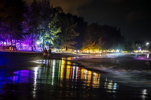 Romantic outdoor photography at a night beach of Phuket, Thailand. Sea shore with colorful illumination and light reflection in sea water of BangTao beach