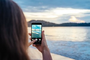 Happy woman taking photos of the sea at sunset with smartphone camera on summer travel vacation to the coast., Phuket island, ThailandBrunette girl making photographie towards the ocean.