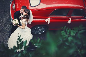 Wedding couple leans on a red car