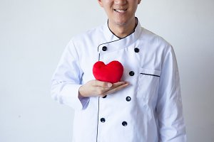 Happy smiling chef holding heart shape with love and passion