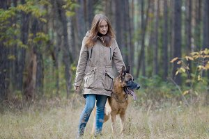Cute girl playing with her pet - german shepherd in autumn park