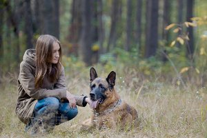 Young woman in autumn park with her pet - german shepherd
