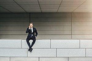 Businessman speaking phone stitting on brick wall