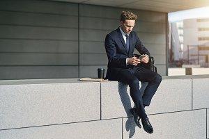 Confident stylish businnessman sitting with his phone