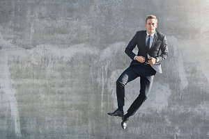 A jumping happy businessman looking at camera