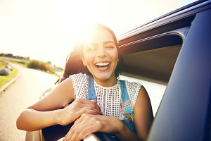 Cute young woman hanging her head from a car