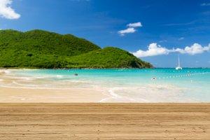 Warm sandy beach in caribbean by wooden decking