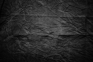 Texture of dark grey crumpled fabric