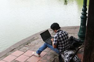 Young man with computer in park