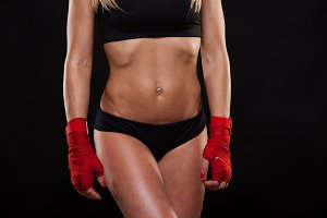 Close view of athletic girl posing in red bandages, isolated on the black background boxing fighter kickbox