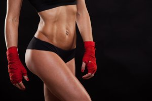 Close up athletic girl posing in red bandages, isolated on the dark background boxing fighter kickbox
