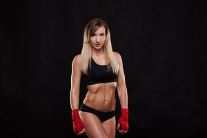 athletic girl posing in red bandages, isolated on the dark background boxing fighter kickbox