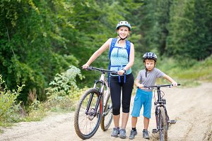 Young woman with son standing with bikes in forest