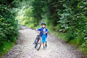Small boy walking with bicycle on mountain trail