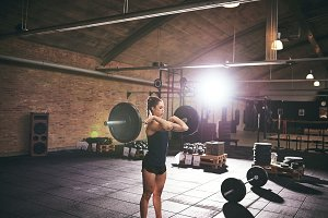 Woman standing with heavy barbell on shoulders