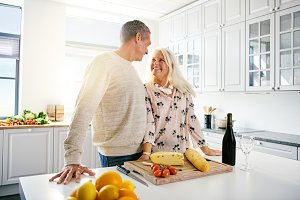 Senior man and woman at kitchen counter with food