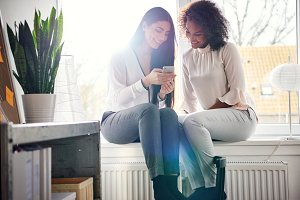 Smiling young women texting a phone message
