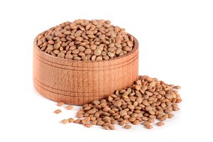 Lentils in a wooden bowl isolated on a white background