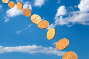 Stream of gold coins falling from blue sky